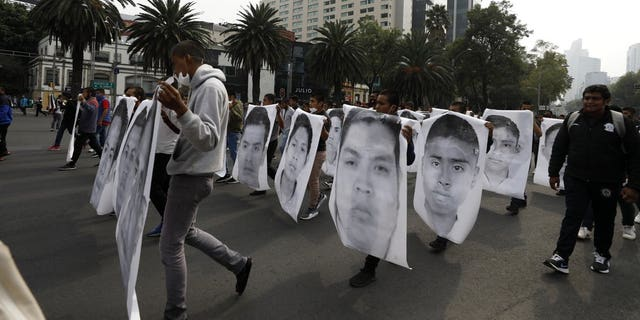 College students join family members of 43 missing students from the Rural Normal School of Ayotzinapa in a march marking the sixth anniversary of the 43 students' enforced disappearance, in Mexico City, 星期六, 九月. 26, 2020. (AP Photo/Rebecca Blackwell)