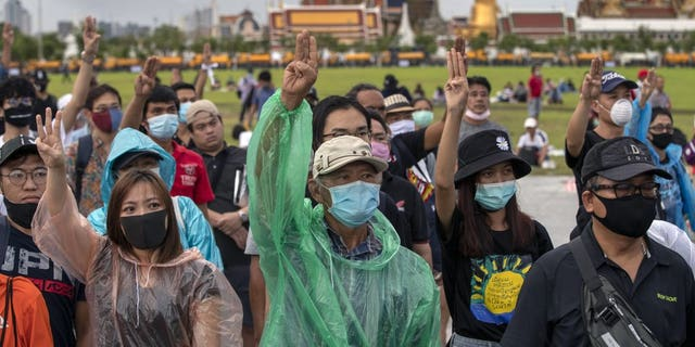 Pro-democracy protesters raise a three-fingers, symbol of resistance salute during a rally at Sanam Luang in Bangkok, Thailand, Sunday, Sept. 20, 2020. Thousands of demonstrators who occupied a historic field in Thailand's capital overnight continued with their rally on Sunday to support the demands of a student-led protest movement for new elections and reform of the monarchy. (AP Photo/Gemunu Amarasinghe)