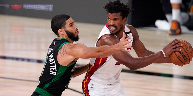 The Boston Celtics' Jayson Tatum, left, defends against the Miami Heat's Jimmy Butler during the second half of an NBA Eastern Conference final playoff basketball game Friday, Sept. 25, 2020, in Lake Buena Vista, Fla. (AP Photo/Mark J. Terrill)