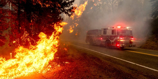 In this Sept. 7 photo, a firetruck drives along state Highway 168 while battling the Creek Fire in the Shaver Lake community of Fresno County, Calif. A weekend wildfire east of Fresno exploded so fast that it trapped hundreds of holiday campers who were airlifted to safety in a dramatic rescue that strained the limits of two California National Guard helicopters. (AP Photo/Noah Berger, File)