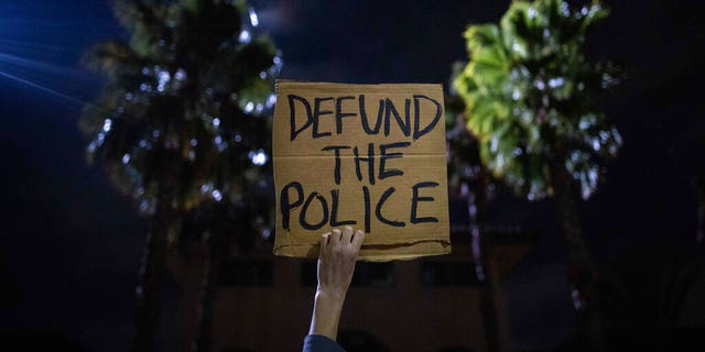 A protester holds up a sign as a police helicopter flies by in front of the South Los Angeles Sheriff's Department during protests following the death of Dijon Kizzee.