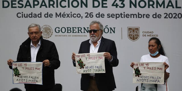 "Mexico's President Andres Manuel Lopez Obrador, 剩下, and Deputy Interior Secretary Alejandro Encinas, 中央, stand with Maria Martinez, mother of Miguel Angel Hernandez Martinez, as they hold cloths embroidered by mothers of some of 43 missing students from the Rural Normal School of Ayotzinapa, with a message reading in Spanish; ""For the 43 and thousands of others, don't fail us, Ayotzinapa,"" following a presentation on the ongoing investigation on the sixth anniversary of the students enforced disappearance, at the National Palace in Mexico City, 星期六, 九月. 26, 2020.(AP Photo/Rebecca Blackwell)"