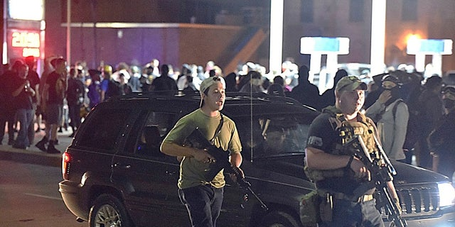 Kyle Rittenhouse, left, with backwards cap, walks along Sheridan Road in Kenosha, Wis., with another armed civilian. (Adam Rogan/The Journal Times via AP, File)