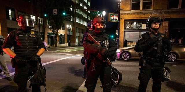 Portland police stand guard in Portland, Ore. The city recorded 488 shootings through Sept. 3, a sharp increase from the 299 shootings for all of 2019. (AP Photo/Paula Bronstein)