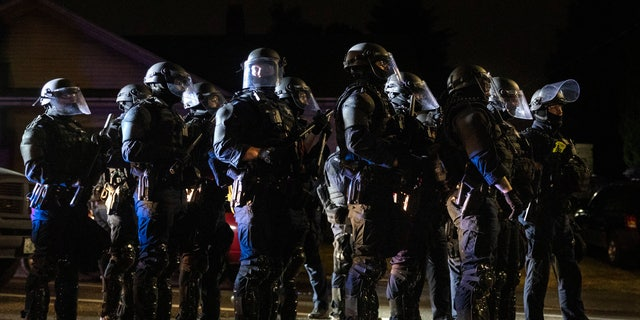Portland police take control of the streets after making arrests on the scene of the nightly protests at a Portland police precinct on Sunday, Aug. 30, 2020, in Portland, Ore. (AP Photo/Paula Bronstein)