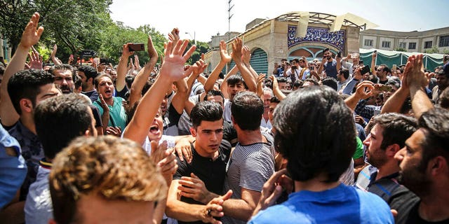 In this June 25, 2018 photo, a group of protesters chant slogans at the main gate of the Old Grand Bazaar, in Tehran, Iran. On Saturday, Sept. 5, 2020, Iran broadcast the televised confession of a wrestler facing the death penalty after a tweet from President Donald Trump criticizing the case. The case of 27-year-old Navid Afkari has drawn the attention of a social media campaign that portrays him and his brothers as victims targeted over participating in protests against Iran's Shiite theocracy in 2018. (Iranian Labor News Agency via AP)