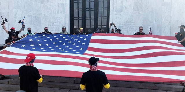 Right-wing protesters unfurl a flag on the steps of Oregon State Capitol for a pro-Donald Trump rally at the Capitol in Salem, Ore. on Monday, Sept. 7, 2020. (AP Photo/Andrew Selsky)