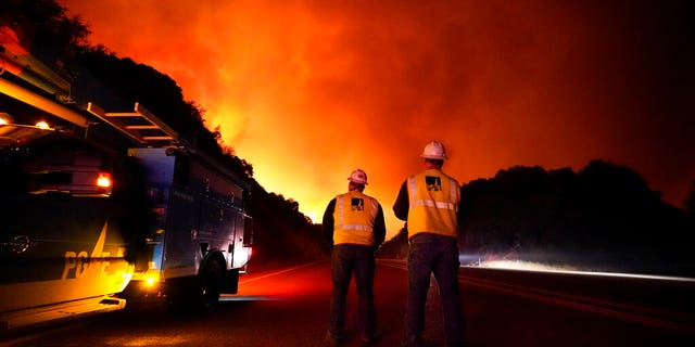 Pacific Gas and Electric workers stand along Highway 168 as the Creek Fire advances Tuesday, Sept. 8, 2020, near Alder Springs, Calif. (AP Photo/Marcio Jose Sanchez)