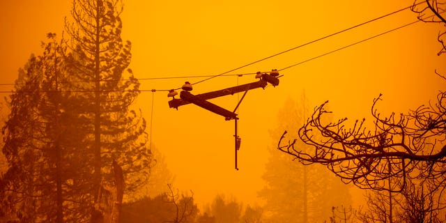 A power line dangles along Auberry Road following the Creek Fire on Tuesday, Sept. 8, 2020, in Fresno County, Calif. (AP Photo/Noah Berger)