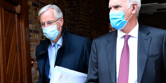 EU Chief negotiator Michel Barnier, left, arrives at St. Pancras international train station in London, Wednesday, Sept. 9, 2020. UK and EU officials begin the eighth round of Brexit negotiations in London. (AP Photo/Alberto Pezzali)