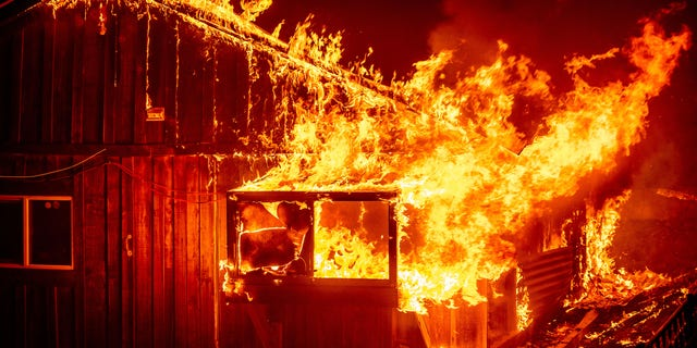 Flames shoot from a home as the Bear Fire burns through the Berry Creek area of Butte County, Calif., on Wednesday, Sept. 9, 2020.