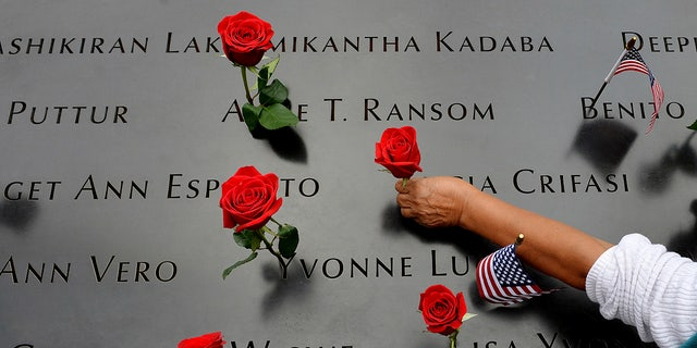 In this Sept. 11, 2014, file photo, a woman places flowers in the inscribed names along the edge of the North Pool during memorial observances on the 13th anniversary of the Sept. 11, 2001 terror attacks on the World Trade Center in New York. The coronavirus pandemic has reshaped how the U.S. is observing the anniversary of 9/11. (AP Photo/Justin Lane, Pool, File)