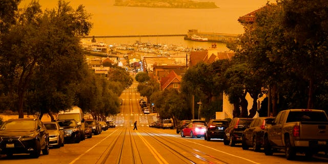 Under darkened skies from wildfire smoke, a man crosses Hyde Street with Alcatraz Island and Fisherman's Wharf in the background Sept. 9, in San Francisco. (AP Photo/Eric Risberg)