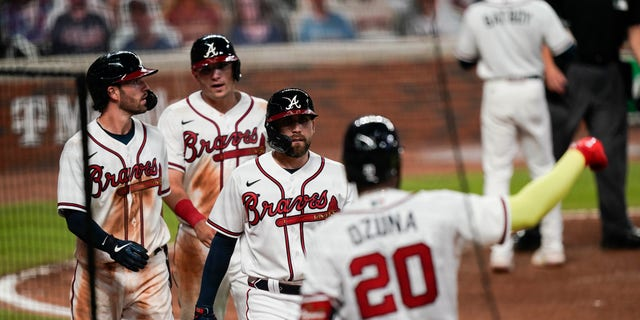 Atlanta Braves' Dansby Swanson, left, Ender Inciarte, center, and Austin Riley return to the bench after scoring in a Ronald Acuna Jr. brace during the sixth inning of a baseball game against the Miami Marlins on Wednesday, September 9, 2020, in Atlanta. (Associated Press)