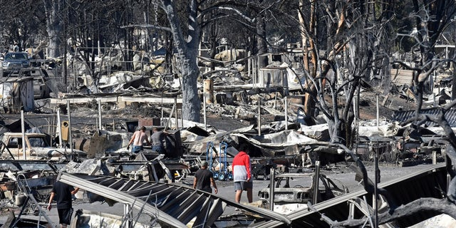 The men walk through the devastated Coleman Creek Estates in Phoenix, Oregon, on Sept. 9.  The Almeda fire, which burned through the cities of Phoenix and Talent in southern Oregon, destroyed about 600 homes, according to the Federal Emergency Management Agency.  (Scott Stoddard / Grants Pass Daily Courier via AP)