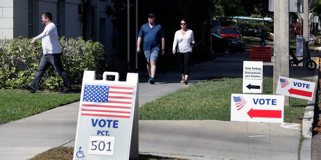 In this March 17, 2020 file photo, voters head to a polling station to vote in Florida's primary election in Orlando, Fla. (AP Photo/John Raoux, File)