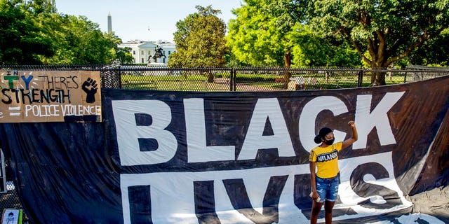 The White House is visible behind a woman who holds her fist up as she poses for a photograph with a large banner that reads Black Lives Matter hanging on a security fence in Washington, after days of protests over the death of George Floyd. June 8, 2020. (AP Photo/Andrew Harnik, File)