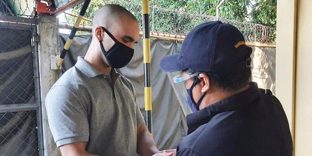 In this photo from the Philippine Immigration Office, U.S. Marine Lance Cpl.  Joseph Scott Pemberton has been handcuffed before leaving Camp Aguinaldo en route to the airport in Quezon, Philippines, Sunday, September 13, 2020.  (Immigration Service via AP)