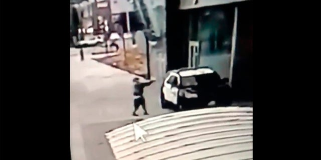 A screen grab from a security camera video released the Los Angeles County Sheriff's Department shows a gunman walking up to sheriff's deputies and opening fire without warning or provocation in Compton, Calif., on Sept. 12. (Los Angeles County Sheriff's Department via AP)