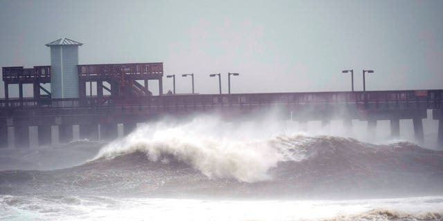 Waves crash near a pier, at Gulf State Park, Sept. 15, in Gulf Shores, Ala. Hurricane Sally is crawling toward the northern Gulf Coast at just 2 mph, a pace that's enabling the storm to gather huge amounts of water to eventually dump on land. (AP Photo/Gerald Herbrt)