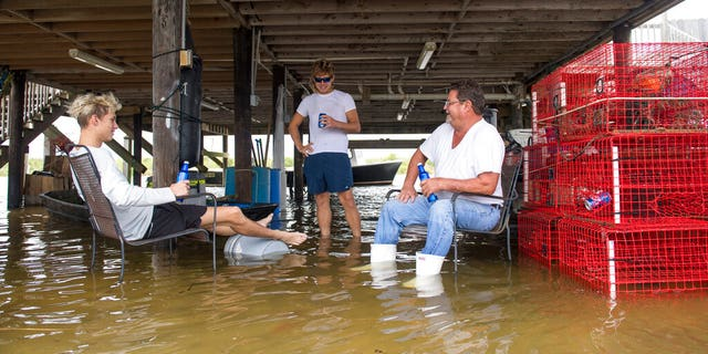Hanging out in flood waters, Cameron Fogg, right, sits by his crab traps as he drinks a beer with Austin Claiborne, 18, left, and Cameron Gomez, center, in Salt Bayou near Slidell, La., on Tuesday, September 15, 2020. Hurricane Sally missed Louisiana, but its effect, such as high water, could be felt along the region. Fogg has lived in this house for 30 years and he said he's getting tired of the recurrence of rising water. (Chris Granger/The Advocate via AP)