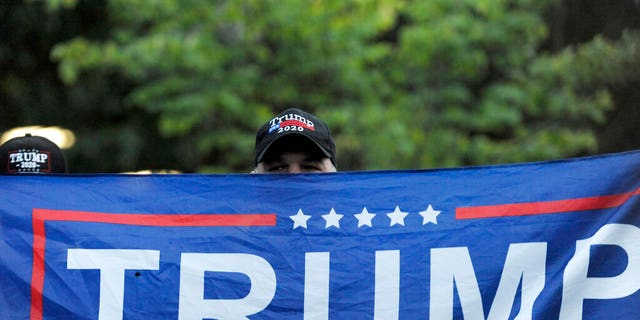 A person holds up a Trump flag at Independence Mall to support U.S. President Donald Trump as he visits the National Constitution Center to participate in the ABC News town hall.