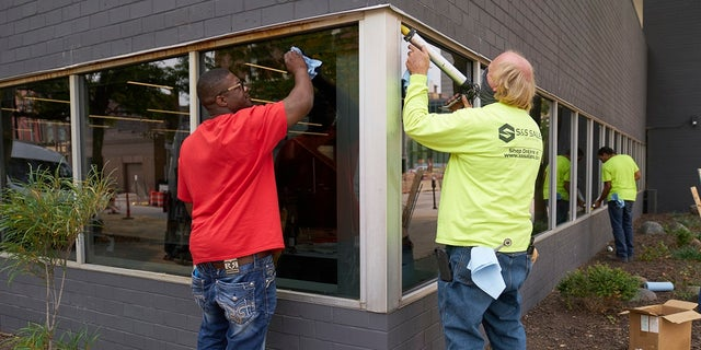 Workers replace windows smashed in May at a business in downtown Omaha, Neb., on Wednesday, one day after a grand jury decided to charge a white business owner who fatally shot Black James Scurlock during civil unrest in downtown Omaha this spring with manslaughter and other charges. (AP Photo/Nati Harnik)