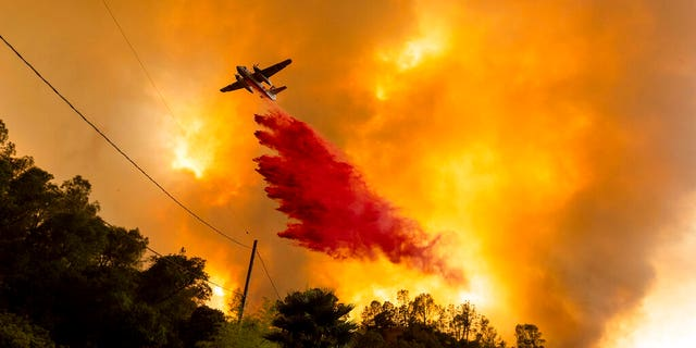 In this Aug. 18 photo, an air tanker drops retardant as the LNU Lightning Complex fires tear through the Spanish Flat community in unincorporated Napa County, Calif. Two unusual weather phenomena combined to create some of the most destructive wildfires the West Coast states have seen in modern times. (AP Photo/Noah Berger, File)