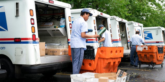 Letter carriers load mail trucks for deliveries at a U.S. Postal Service facility in McLean, Va. (AP Photo/J. Scott Applewhite)