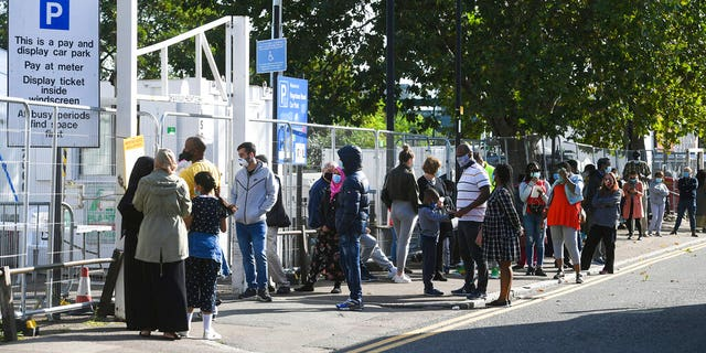 People queue up outside a coronavirus testing centre offering walk-in appointments in north London, Friday Sept. 18, 2020.  (Kirsty O'Connor/PA via AP)