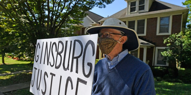 A protester stands outside the house of Senate Majority Leader Mitch McConnell, R-Ky., in Louisville, Ky., Saturday, Sept. 19, 2020. McConnell vowed on Friday night, hours after the death of Supreme Court Justice Ruth Bader Ginsburg to call a vote for whomever President Donald Trump nominated as her replacement. (AP Photo/Timothy D. Easley)