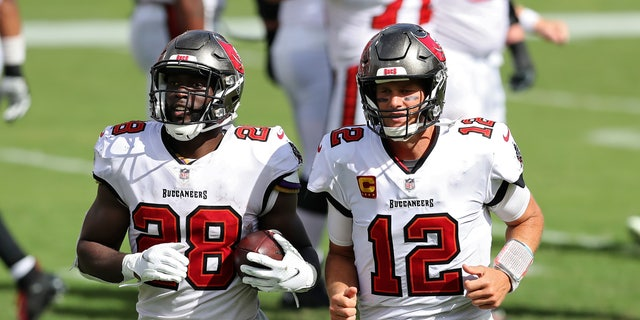Tampa Bay Buccaneers running back Leonard Fournette (28) runs off the field with quarterback Tom Brady (12) after Fournette ran 46-yards for a score against the Carolina Panthers during the second half of an NFL football game Sunday, 씨족. 20, 2020, 탬파, Fla. (AP Photo/Mark LoMoglio)