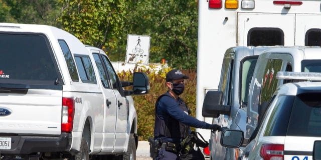 A Royal Canadian Mounted Police officer walks outside of an apartment complex Monday, Sept. 21, 2020, in St-Hubert, Quebec, during a raid in connection with an envelope containing the poison ricin, which was addressed to the White House.