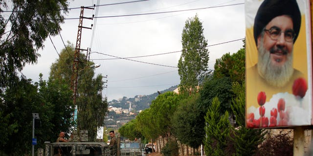 Lebanese army vehicles pass next to a portrait of Hezbollah leader Sayyed Hassan Nasrallah, as they patrol on a road that leads to the site of an explosion that rocked a Hezbollah stronghold, in the southern village of Ain Qana, Lebanon, Tuesday, Sept. 22, 2020. (AP Photo/Mohammed Zaatari)