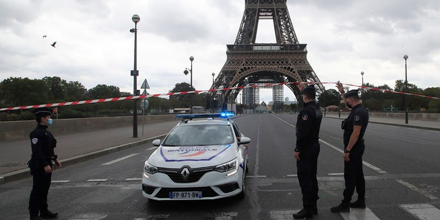 French police officers secure the bridge leading to the Eiffel Tower, Wednesday, Sept. 23, 2020, in Paris. Paris police have blockaded the area around the Eiffel Tower after a phone-in bomb threat. (AP Photo/Michel Euler)