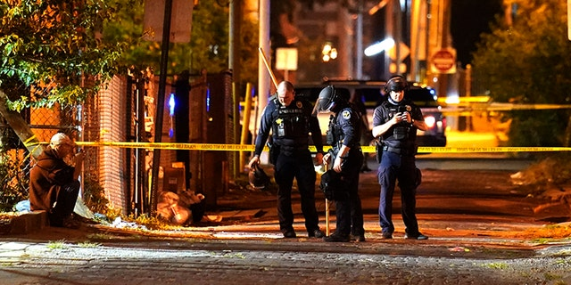 Police survey an area after a police officer was shot, Wednesday, Sept. 23, 2020, in Louisville, Ky. (Associated Press)