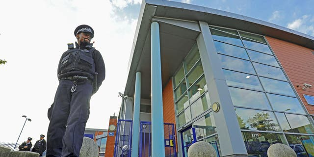 A police officer stands in front of the Croydon Detention Center, where a police officer was shot dead in the early hours of Friday, September 25, 2020, in Croydon, England.  (Associated Press)