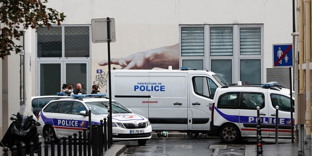 Police car park outside a building after four people have been wounded in a knife attack near the former offices of satirical newspaper Charlie Hebdo on Sept. 25, 2020 in Paris. (AP Photo/Thibault Camus)
