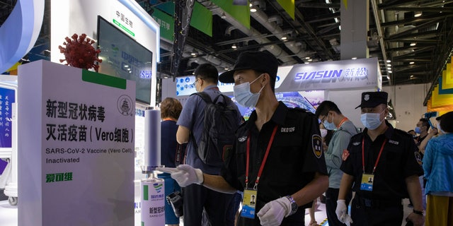 Chinese security guard walk past a giant replica of the COVID-19 vaccine produced by Sinopharm subsidiary CNBG displayed during a trade fair in Beijing on Sunday, Sept. 6, 2020. State-backed Sinopharm's subsidiary CNBG has injected 350,000 people outside its clinical trials for COVID-19 vaccine, which have about 40,000 people enrolled. It's a highly unusual move that raises ethical and safety questions, as companies and governments worldwide race to develop a vaccine that will stop the spread of the new coronavirus. (AP Photo/Ng Han Guan)