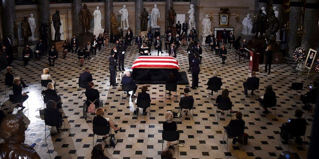 A U.S. Capitol Police honor guard surrounds the flag-draped casket of Justice Ruth Bader Ginsburg as lies in state in Statuary Hall of the U.S. Capitol, Friday, Sept. 25, 2020, in Washington. (Olivier Douliery/Pool via AP)