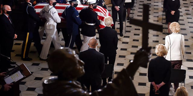 A joint services military honor guard carries the flag-draped casket of Justice Ruth Bader Ginsburg to lie in state in Statuary Hall of the U.S. Capitol, Friday, Sept. 25, 2020, in Washington. (Olivier Douliery/Pool via AP)