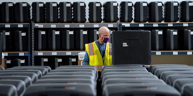 In this Sept. 3, 2020, file photo, a worker prepares tabulators for the upcoming election at the Wake County Board of Elections in Raleigh, N.C. (AP Photo/Gerry Broome, file)