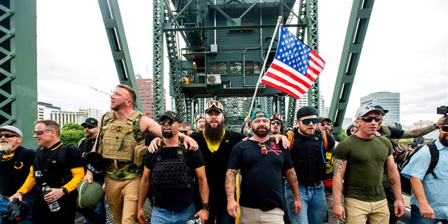 Members of the Proud Boys and other right-wing demonstrators march across the Hawthorne Bridge during a rally in Portland, Ore. (AP Photo/Noah Berger, File)