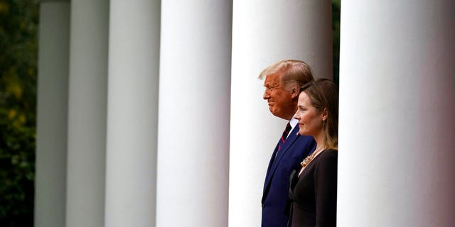 President Donald Trump walks with Judge Amy Coney Barrett to a news conference to announce Barrett as his nominee to the Supreme Court, in the Rose Garden at the White House, Sept. 26, in Washington.