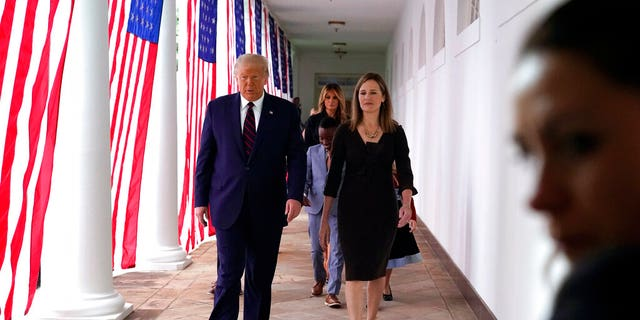 President Trump walks along the Colonnade with Judge Amy Coney Barrett after a news conference to announce Barrett as his nominee to the Supreme Court, in the Rose Garden at the White House, Saturday, Sept. 26, 2020, in Washington. (AP Photo/Alex Brandon)