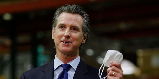 FILE: Gov. Gavin Newsom holds a face mask as he urges people to wear them to fight the spread of the coronavirus during a news conference in Rancho Cordova, Calif.