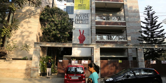 FILE - In this Tuesday, Feb. 5, 2019, file photo, a woman walks past the Amnesty International India headquarters in Bangalore, India. The Human rights watchdog said on Tuesday, Sept. 29, 2020, that it was halting its operation in India, citing reprisals from the government and the freezing of its bank accounts. Its announcement comes at a time amid growing concerns over the state of free speech in India where critics accuse Prime Minister Narendra Modi and his Hindu nationalist government of increasingly brandishing laws to silence human rights activists, intellectuals, filmmakers, students and journalists. (AP Photo/Aijaz Rahi, File)