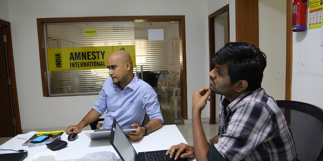 FILE - In this Tuesday, Feb. 5, 2019, 档案照片, Amnesty International India employees work at their headquarters in Bangalore, India. (AP Photo/Aijaz Rahi文件le)