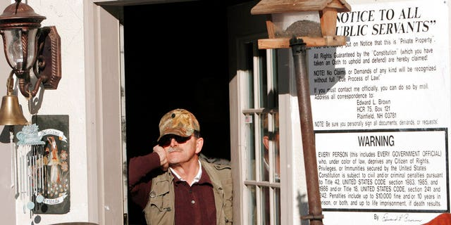 In this Jan. 17, 2007 photo, Edward Brown stands barricaded in the doorway of his home in Plainfield, N.H., saying he is prepared for an armed standoff. Brown was up for re-sentencing Tuesday Sept. 29, 2020 over a months long armed standoff with U.S. marshals in 2007 to protest a tax evasion conviction. (AP Photo/Jim Cole, File)