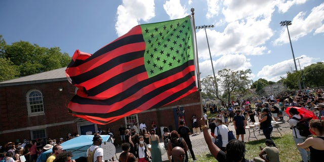A stylized American Black Lives Matter flag flies during a Juneteenth rally, Friday, June 19, 2020, in Boston. Juneteenth commemorates when the last enslaved African Americans learned in 1865 they were free, more than two years following the Emancipation Proclamation. (AP Photo/Michael Dwyer)